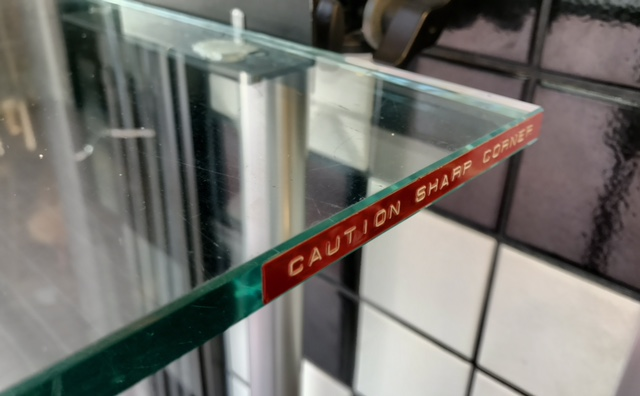 "Glass shelf with a sharp corner and a label saying ""caution sharp corner"""
